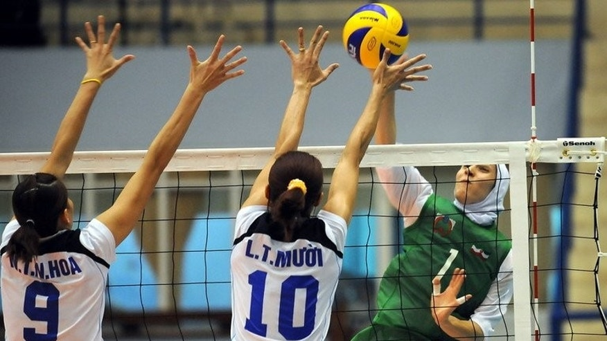 Vietnam's Nguyen Thi Ngoc Hoa (left) and Le Thi Muoi (centre) try to block a shot from Iran's Vahedi Langroodi Zahra during a match at the 15th Asian Senior Women's Volleyball championship in Hanoi on September 13, 2009. Iran's volleyball triumph has created a dilemma for the state broadcaster, which is struggling to tailor its coverage of matches attended by scantily dressed women.