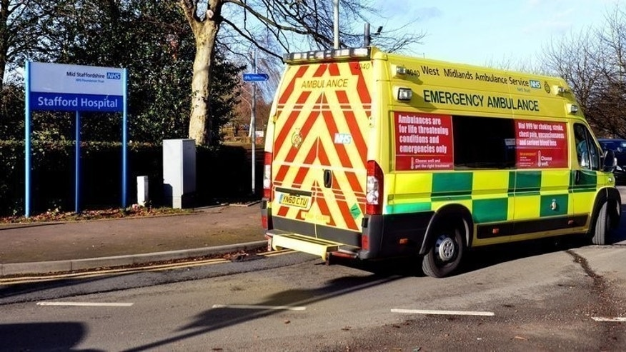 An ambulance being driven past a sign at Stafford Hospital in Stafford, central England on February 4, 2013. Britain announced plans on Wednesday to charge migrants hundreds of pounds a year to access its state-run National Health Service (NHS), in a bid to clamp down on so-called health tourism.