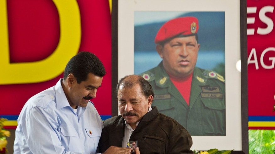 Venezuela's President Nicolas Maduro gives a present to Nicaragua's President Daniel Ortega during opening session of the 8th Petrocaribe Summit in Managua, Nicaragua, June 29, 2013.