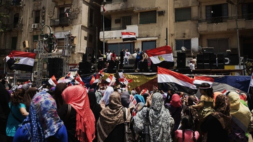"""Egyptians cheer and wave their national flag as they gather in Cairo's landmark Tahrir Square on July 4, 2013. Governments across the Middle East have welcomed the ouster of Egypt's Islamist president Mohamed Morsi with varying degrees of enthusiasm, with war-hit Syria calling it a """"great achievement""""."""