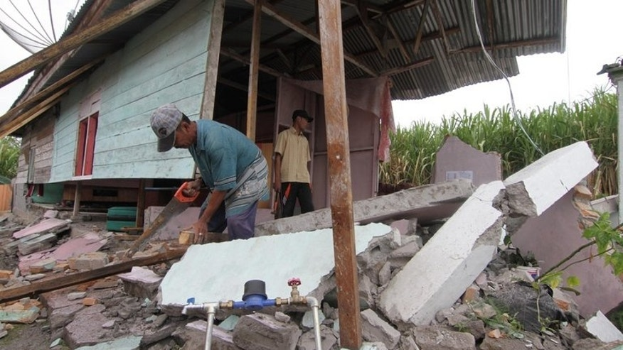 Acehnese residents check damage to their house in Blang Mancung, in the highlands of Aceh province, on July 4, 2013. Aid has begun to trickle in to devastated villages in Aceh province where thousands have been left homeless after a powerful earthquake that killed at least 30 people.