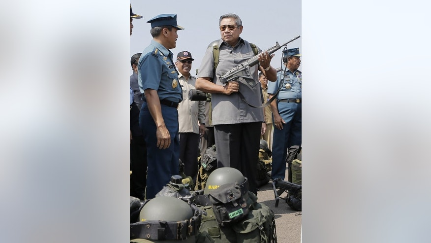 Indonesian President Susilo Bambang Yudhoyono holds a firearm while visiting troops at the Halim Perdanakusuma airport in Jakarta on June 25, 2013. Despite Canberra's tough new policies banishing asylum-seekers to remote Pacific islands, thousands of would-be refugees continue to make the sea crossing to Australia, often from transit hubs in Indonesia.
