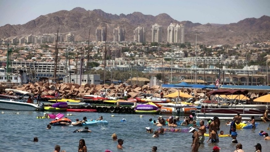 Tourists enjoy the beach in the Red Sea Israeli resort city of Eilat on August 19, 2011. Several explosions were heard Thursday night in Eilat near the Egyptian border, a police spokesman said, adding that the source of the blasts was not known.