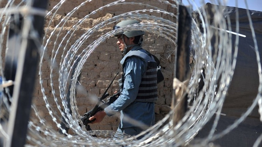 An Afghan policeman patrols in Helmand Province on June 19, 2012. A bomb attack killed four girls attending an Afghan wedding, officials said Thursday, blaming the attack on Taliban rebels intending to target government employees at the event.