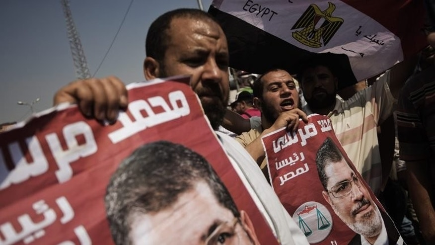 Muslim Brotherhood supporters hold posters of Egyptian President Mohammed Morsi during a rally outside the Rabaa El-Adaweya mosque in Cairo, on July 2, 2013. Having waited for over 80 years, Egypt's Muslim Brotherhood secured power when Morsi was elected president, but it can only blame itself after being ousted just 12 months later, analysts say.