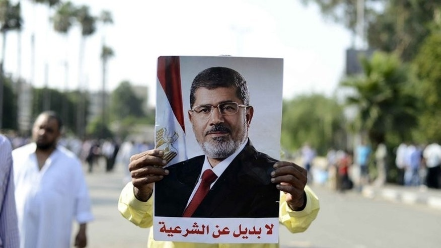 A Muslim Brotherhood supporter holds a picture of Mohamed Morsi during a rally outside Cairo University, on June 2, 2013. Having waited for over 80 years, the Muslim Brotherhood secured power when Morsi was elected president, but it can only blame itself after being ousted just 12 months later, analysts say.