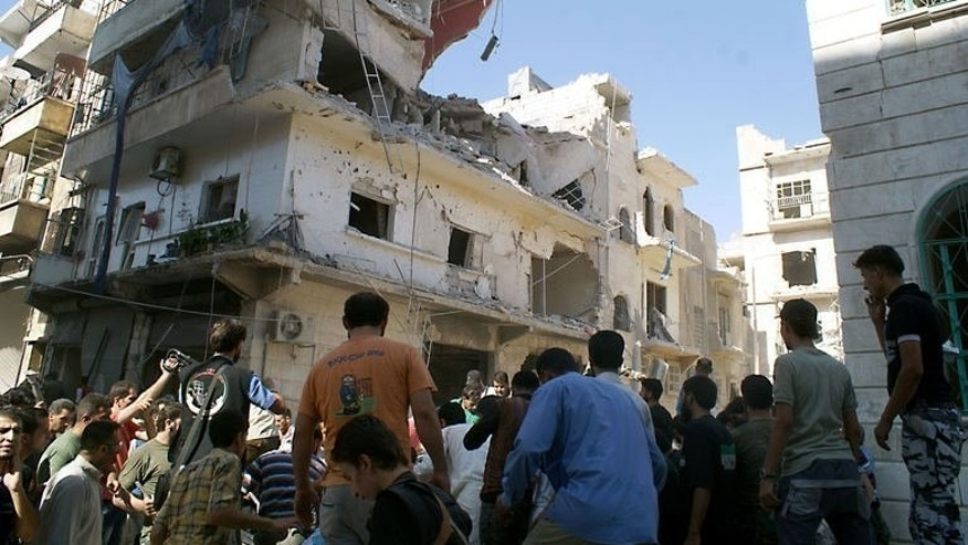 Rescuers and neighbors gather at the scene after a rocket slammed into the side of a residential building in the northern city of Aleppo, on June 29, 2013. Syria's main opposition has warned that the fall of Homs to regime forces could scupper any hope of a political solution to the civil war.