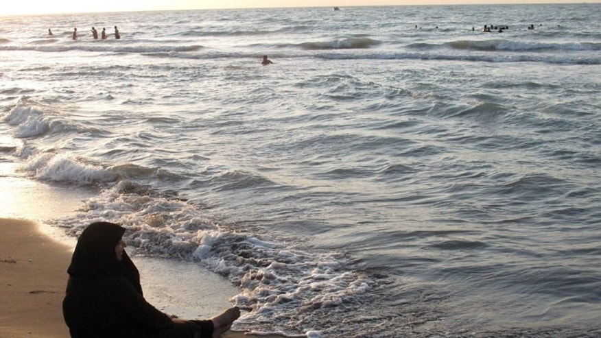 An Iranian woman sits along the shores of the Caspian Sea, on July 28, 2011. An Iranian woman has claimed that the authorities in the Islamic republic have denied her a free water swimming record after saying that her costume failed to meet the standards of sharia law.