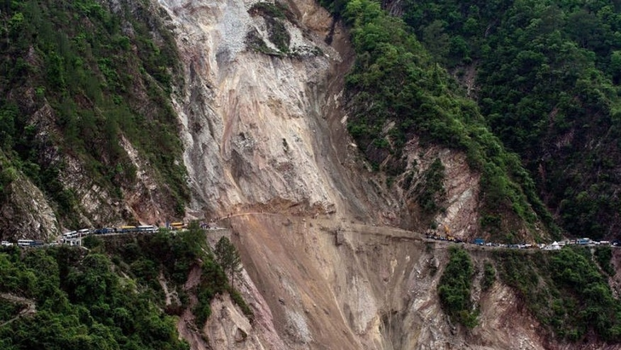 In this picture taken June 25, 2013, vehicles wait on the either side of a road -- linking Rudraprayag and Srinagar -- that was destroyed by a landslide in northern India. Landslides and floods triggered by several weeks of monsoon rains have killed at least 50 people in mainly remote parts of Nepal, a government official said Thursday.