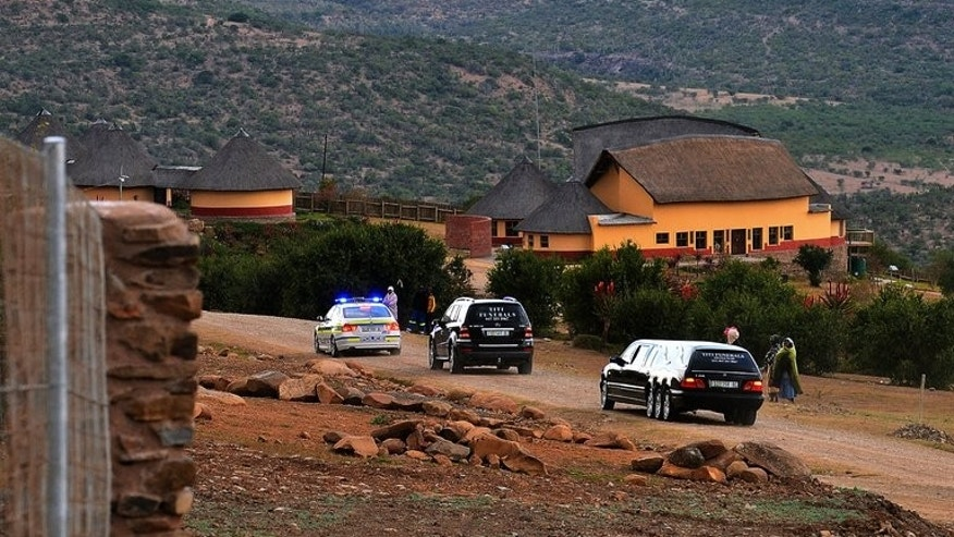 A police convoy and hearse arrive at Mvezo resort to collect the remains of former South African President Nelson Mandela's children on July 3, 2013. The exhumed remains of the three children at the centre of an ugly family feud were due to undergo forensic tests before reburial in the ailing anti-apartheid hero's childhood village.