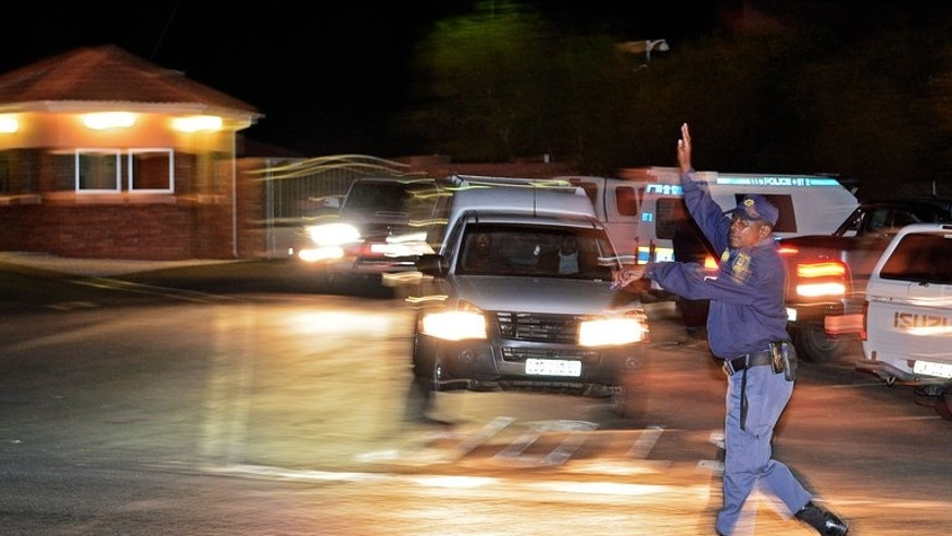 Police stop traffic outside Nelson Mandela's home in Qunu on July 3, 2013. The exhumed remains of three of Mandela's children at the centre of an ugly family feud are due to undergo forensic tests before reburial in the ailing anti-apartheid hero's childhood village.