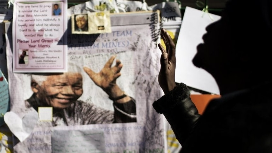 "A man prays in front of a picture of Nelson Mandela outside the Pretoria hospital where he is staying, on July 4, 2013. Haunted by death during his long anti-apartheid struggle, Mandela looked toward his own ""eternal sleep"" as a man who fulfilled his duty to his people."