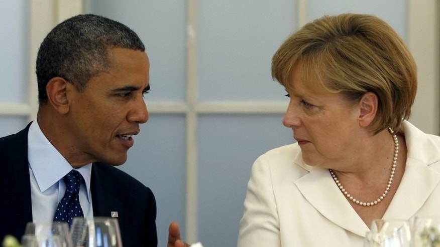 US President Barack Obama and German Chancellor Angela Merkel chat during a dinner in Berlin,on June 19, 2013. Obama has spoken with Merkel to address mounting European concerns about broad US surveillance programs.