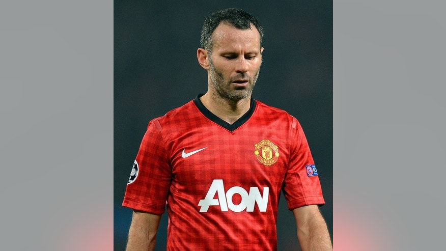 Manchester United's Ryan Giggs leaves the field during the match against Real Madrid in Manchester, on March 5, 2013. New Manchester United manager David Moyes has drafted trophy-winning expertise into the dug-out in the shape of veteran midfielder Giggs, United's most decorated player, and former Old Trafford stalwart Phil Neville.