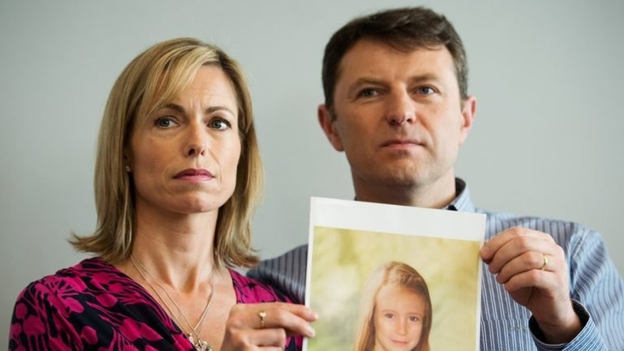 """Parents of missing girl Madeleine McCann, Kate (L) and Gerry McCann (R) pose with an artist's impression of how their missing daughter might look on May 2, 2012. Police are opening their own investigation into the toddler's 2007 disappearance in Portugal and have identified 38 """"persons of interest"""" across Europe."""