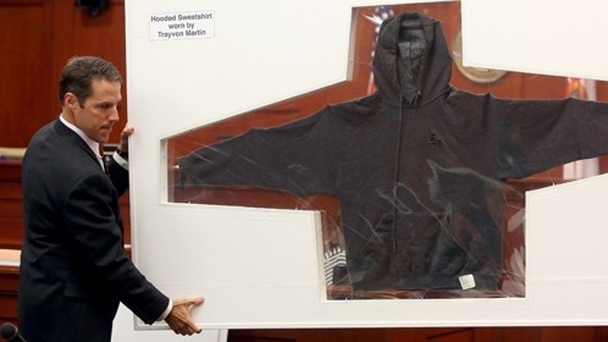 Assistant state attorneys John Guy, left, and Bernie de la Rionda, right, display the hooded sweatshirt worn by Trayvon Martin the night he was shot by George Zimmerman during Zimmerman's trial in Seminole County circuit court, in Sanford, Fla., Wednesday, July 3, 2013. Zimmerman is charged with second-degree murder in the fatal shooting of Trayvon Martin, an unarmed teen, in 2012. (AP Photo/Orlando Sentinel, Jacob Langston, Pool)