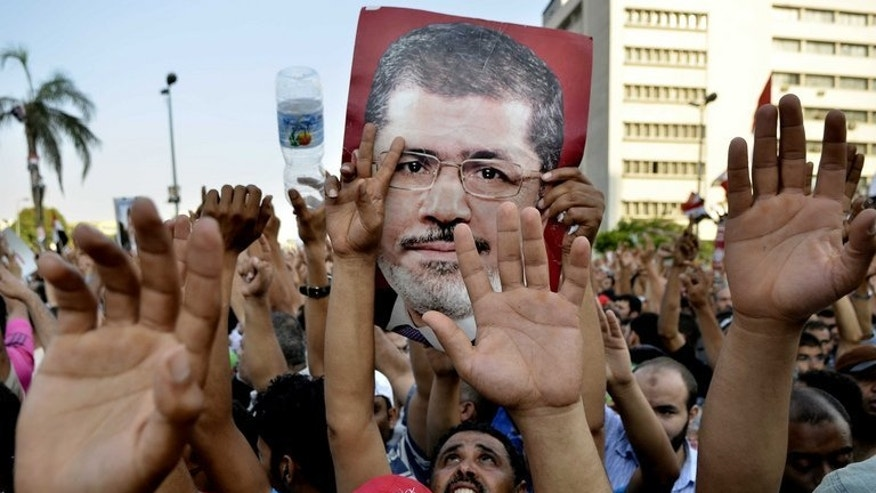 Supporters of the Muslim Brotherhood hold pictures of deposed president Mohamed Morsi as they shout slogans during a demonstration outside the Republican Guards headquarters in Cairo on July 5, 2013. At least 26 people were killed in clashes across Egypt as tens of thousands of supporters of Morsi turned out to protest his ouster by a popularly backed military coup