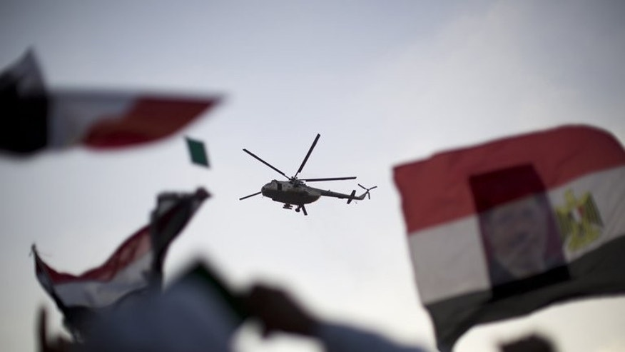 An Egyptian military helicopter hovers over supporters of the Muslim Brotherhood during a rally in support of deposed president Mohamed Morsi outside Cairo's Rabaa al-Adawiya mosque on July 5, 2013. At least 26 people were killed in clashes across Egypt as tens of thousands of supporters of Morsi turned out to protest his ouster by a popularly backed military coup.