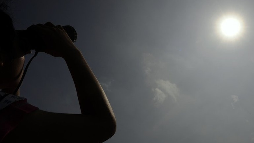 A woman in Hong Kong looks through binoculars as planet Venus orbits between the Sun and the Earth on June 6, 2012. British astronomers have set up an experts' network to promote the search for extraterrestrial intelligence, the Royal Astronomical Society said on Friday.