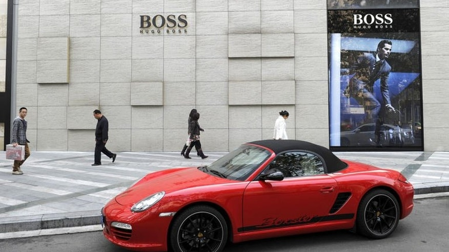 Pedestrians walk in front of a fashion store as a luxury sports car is parked nearby in Chengdu, the capital of China's southwestern province of Sichuan on November 23, 2011. A man who crashed a car on average every three days for almost three years in a Chinese insurance scam has been arrested, media reported Friday.