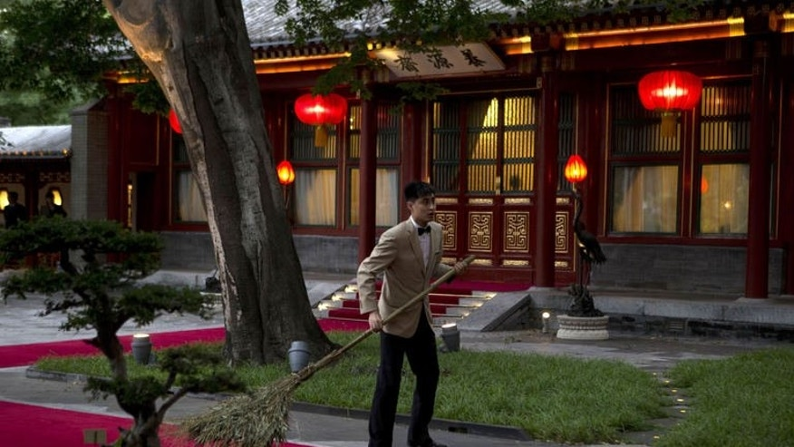 A Chinese attendant prepares for the arrival of Pakistan Prime Minister Nawaz Sharif at the Diaoyutai State guest house in Beijing on July 4, 2013.