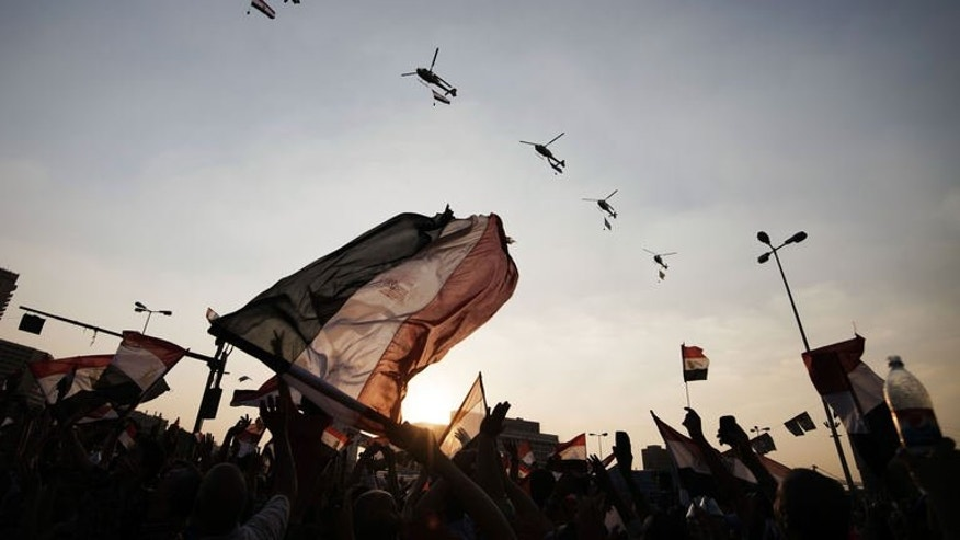 Egyptian people wave the national flag as army helicopters fly above Egypt's landmark Tahrir square on July 4, 2013. Egypt's controversial public prosecutor Abdel Meguid Mahmud said Friday he was to resign, days after being reinstated, citing possible conflicts of interest in future prosecutions.