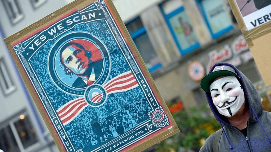 "A protester wearing a Guy Fawkes mask holds a banner with a picture of US President Barack Obama to protest against the US surveillance programme ""PRISM"" on June 29, 2013 in Hanover, central Germany. European Union officials head into complex security talks in Washington on Monday threatening to suspend key data-swapping deals with the United States amid anger over reports of US snooping."