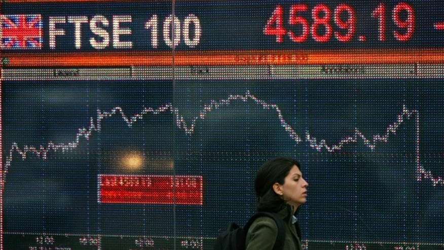 A woman walks past an electronic sign showing the FTSE 100 index in London in October 2008.