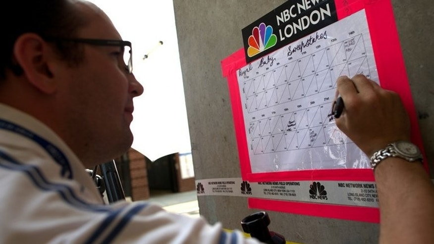 Members of the media mark up their selections for a sweepstake on the time, date and sex of the royal baby outside the Lindo wing of St Mary's Hospital in London on July 5, 2013.
