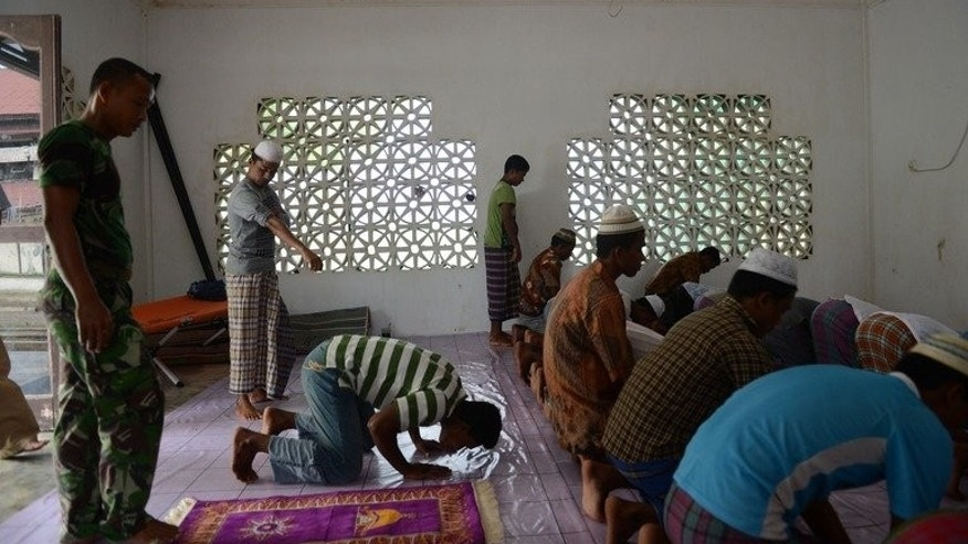 An Indonesian soldier (L) joins a group of Rohingya asylum-seekers from Myanmar for prayers in a mosque at the immigration detention center in Lhokseumawe town, Aceh province, on April 11, 2013. Buddhist-majority Myanmar views its population of roughly 800,000 Rohingya as illegal Bangladeshi immigrants, and as sectarian violence has escalated in the past year they have fled in increasing numbers.