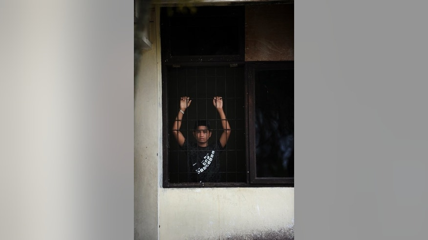 A young Rohingya asylum-seeker from Myanmar looks through a window of the immigration detention center in Lhokseumawe town, Aceh province, on April 11, 2013. Most Rohingya do not initially view Indonesia as their final destination and hope to use it as a stopping point en route to Australia, where more than 220 have arrived on asylum seeker boats over the past year.