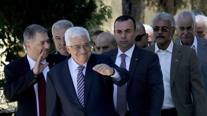 Palestinian leader Mahmud Abbas (third right) waves as he arrives among other officials for a visit at a cemetery for Palestinian refugees just outside the camp of Sabra and Shatila, in southern Beirut on July 5, 2015. Abbas paid a rare visit on Friday to a Palestinian refugee camp in Lebanon, placing a wreath at the cemetery in the Shatila camp in the capital Beirut.