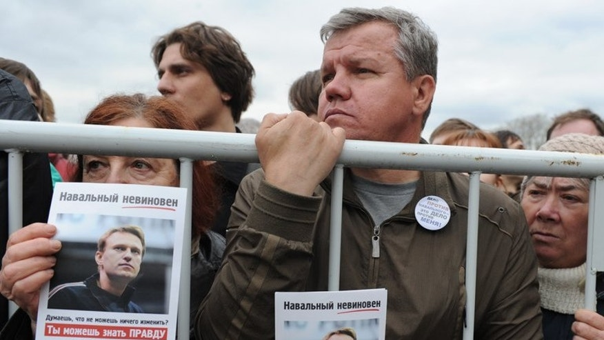 Protesters hold posters depicting opposition leader Alexei Navalny at a rally in central Moscow, on May 6, 2013 to denounce President Vladimir Putin. A Russian prosecutor on Friday demanded a six-year jail sentence for Russia's top opposition leader for embezzlement charges in a case he says is politically motivated.