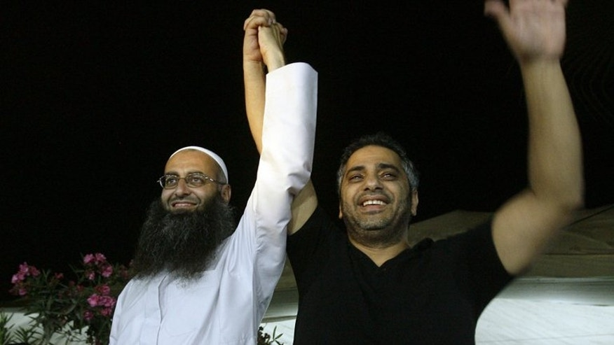 Lebanese Sunni Muslim Salafist cleric Sheikh Ahmed al-Assir (left) holding the hand of singer Fadel Shaker in the southern city of Sidon on July 27, 2012. Several hundred people protested in the southern Lebanese city of Sidon on Friday in support of Ahmed al-Assir, a radical cleric on the run since deadly clashes between his supporters and the army.