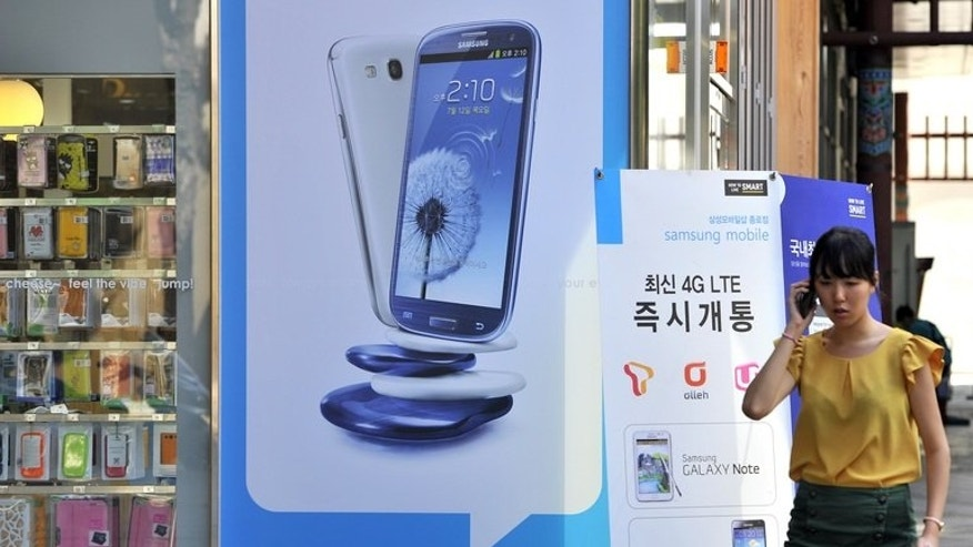 A woman walks past a Samsung Galaxy sign at a mobile phone shop in Seoul on August 27, 2012. Samsung Electronics Co. said Friday it expected to post a record quarterly operating profit of 9.5 trillion won ($8.3 billion) in the second quarter of this year.