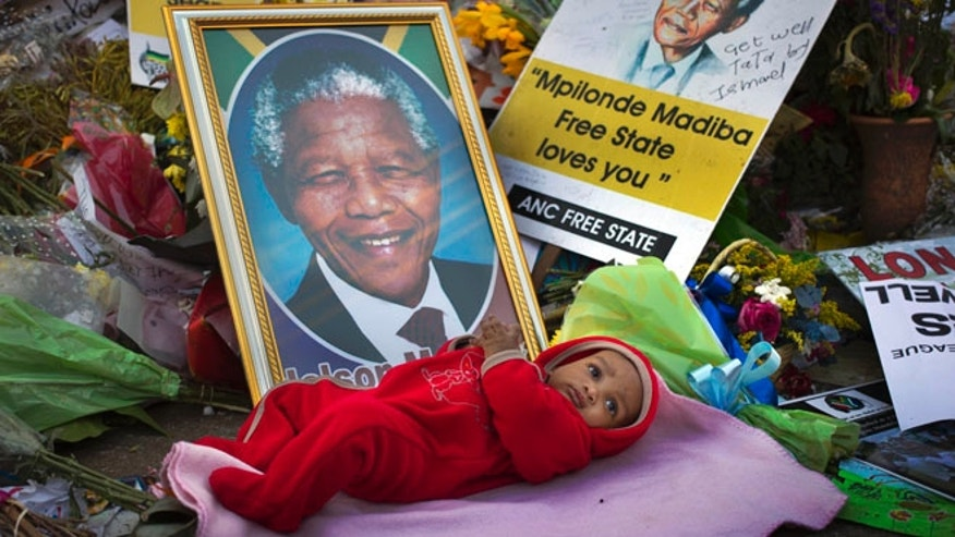 July 4: A 4-months-old is placed by his mother next to a picture of Nelson Mandela outside the Mediclinic Heart Hospital where the former South African president is being treated in Pretoria, South Africa.