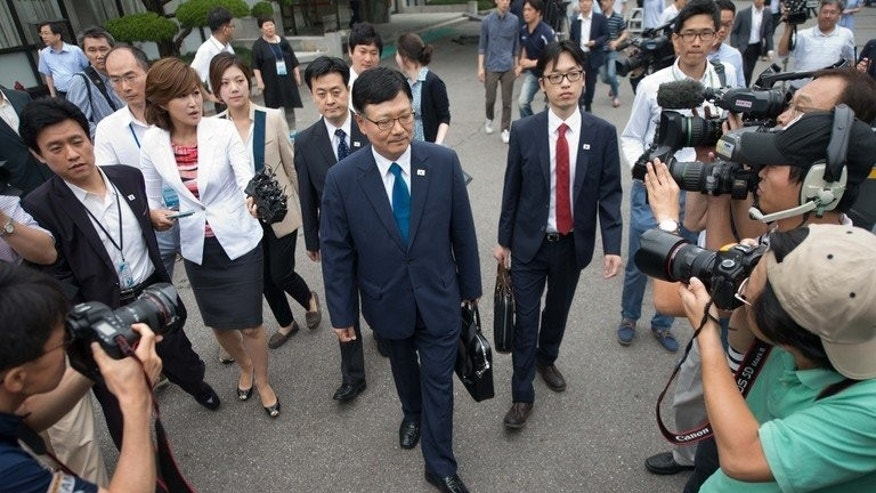 Suh Ho (C), the head of a South Korean working-level delegation, walks with colleagues as they prepare to depart for the North Korean border village of Panmunjom, from the Office of the South Korea-North Korea Dialogue in Seoul, on July 6, 2013. The two Koreas agreed to hold working-level talks aimed at restarting the joint Kaesong industrial complex.