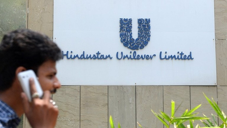 A pedestrian talks on his mobile phone as he walks past the offices of Hindustan Unilever Limited in Mumbai on April 30, 2013. Unilever said it has paid $3.2 billion for an additional 14.8 percent in its Indian subsidiary as part of its strategy of expanding in emerging markets.
