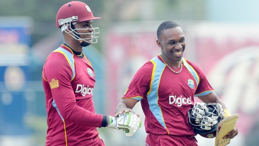 Dwayne Bravo (right) and Marlon Samuels leave the field after West Indies beat Sri Lanka in Kingston on June 28. West Indies captain Dwayne Bravo won the toss and put India in to bat in the fourth match of the Celkon Mobile Cup Tri-Nation Series at Queen's Park Oval on Friday.