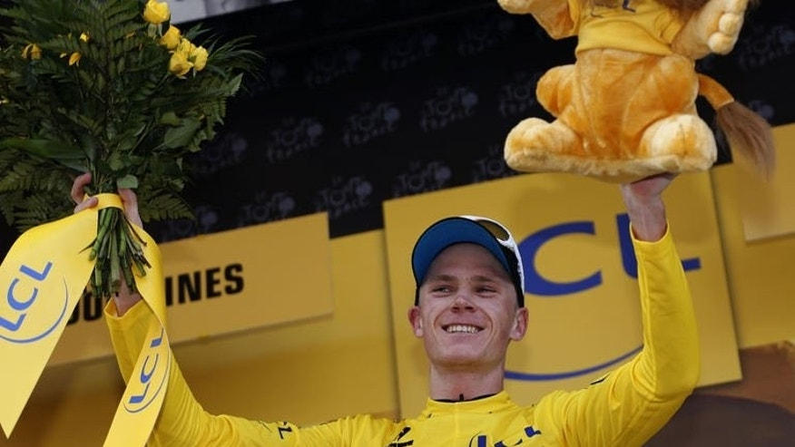 "Britain's Christopher Froome celebrates his overall leader's yellow jersey on the podium at the end of the 195 km eighth stage of the 100th edition of the Tour de France cycling race on July 6, 2013. Froome fired a broadside at a cycling generation tainted by doping scandals as he insisted he is racing ""100 percent"" clean at the world's biggest and most notorious bike race."
