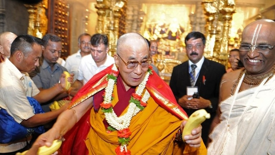 "The Dalai Lama (C) gives bananas to photographers covering his visit to the ISKCON temple in Bangalore on July 5, 2013. The spiritual leader said he was counting on young people to create a ""happier"" century as he celebrated his 78th birthday in southern India with tens of thousands of fellow Tibetan exiles."