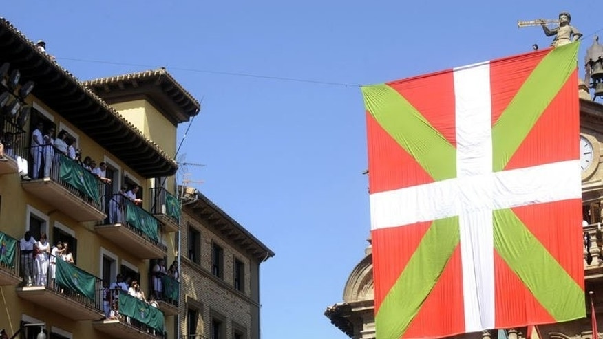 A giant Basque flag hangs on the Town Hall of Pamplona, northern Spain, before the start of the San Fermin Festival on July 6, 2013. Crowds in red and white erupted in cheers to launch the annual bull-running festival but only after a 19-minute delay caused by a giant Basque flag that blocked the starting rocket.