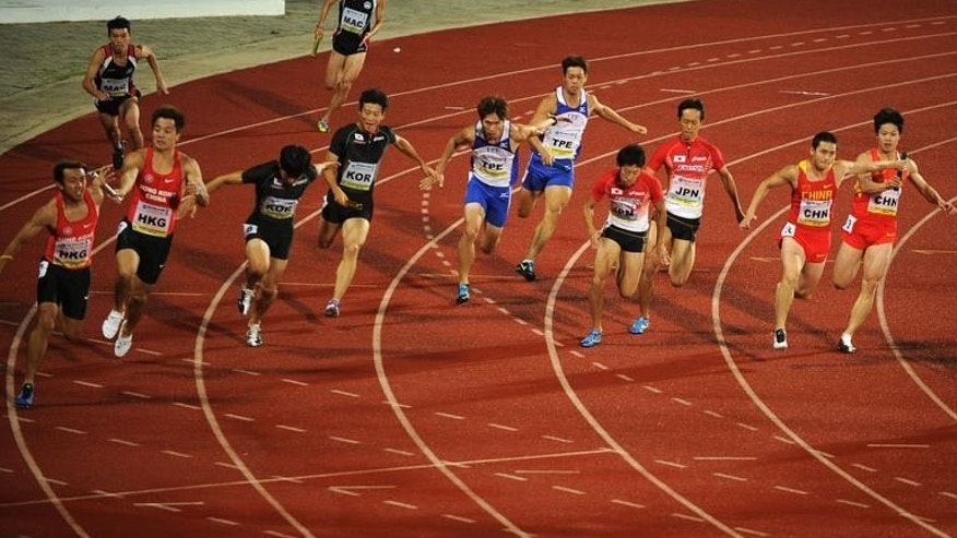 Sprinters hand over batons during the men's 4 x 100 metres relay on the fourth day of the Asian Athletics Championship 2013 at the Chatrapati Shivaji Stadium in Pune on July 6, 2013.