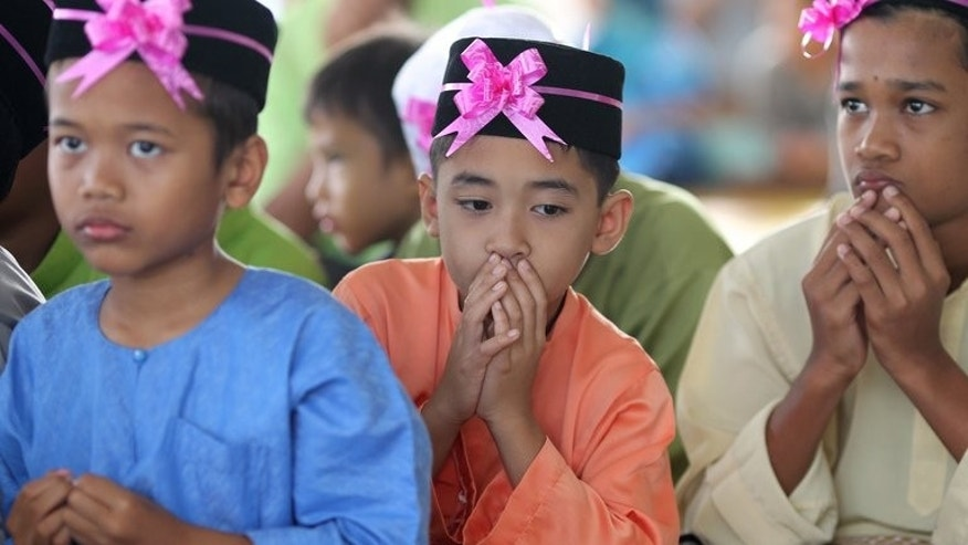 This file photo shows boys praying during a ceremony in Kajang, outside Kuala Lumpur, on November 20, 2011. Malaysia has withdrawn an Islamic law which allows one parent to give consent for the religious conversion of a child, reports said on Saturday, after an outcry that it discriminated against minorities.