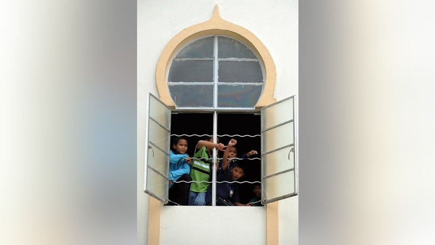 This file photo shows children standing by a window of a mosque in Kuala Lumpur, on January 8, 2010. Malaysia has withdrawn an Islamic law which allows one parent to give consent for the religious conversion of a child, reports said on Saturday, after an outcry that it discriminated against minorities.