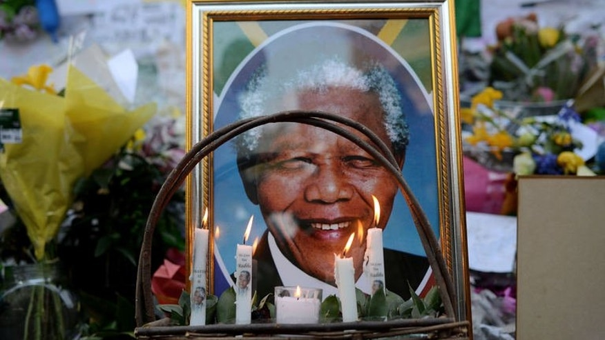 Candels are seen burning by a portrait of Nelson Mandela outside of the Mediclinic Heart hospital in Pretoria on July 6, 2013.