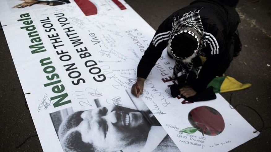 A man signs a poster with messages for former South African president Nelson Mandela, outside the Medi Clinic Heart Hospital where he lay in critical condition in Pretoria on July 6, 2013.