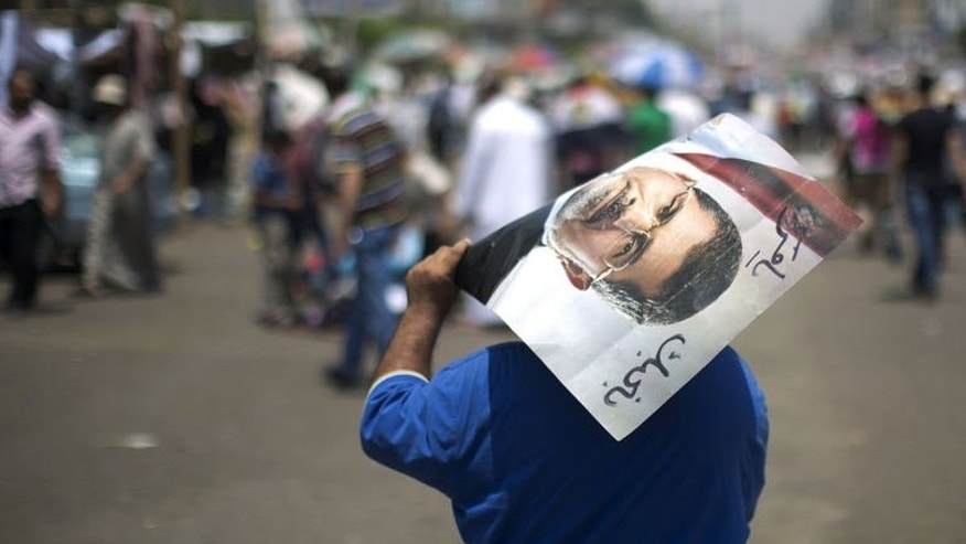 An Egyptian supporter of the Muslim Brotherhood walks holding a poster featuring deposed president Mohamed Morsi during a rally to support him on July 6, 2013 outside Cairo's Rabaa al-Adawiya mosque. The ouster by the army of Morsi has crushed the dreams of Gaza's Hamas rulers, who will now have to build ties with the new Egyptian authorities, analysts say.