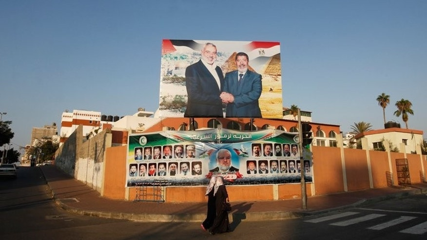 "Palestinian girls walk in front of a photograph of Egyptian President Mohammed Morsi (R) shaking hands with the Palestinian Hamas leader Ismail Haniya, in Gaza City on August 29, 2012. ""Do not fear for the Palestinian cause or for the resistance (against Israel) or for Gaza. Egypt is behind us, as are the Arab and Islamic countries,"" Haniya said in a Friday sermon."