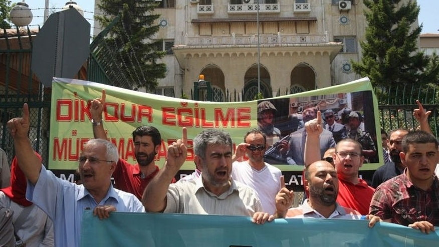 "Turkish supporters of ousted Egyptian President Mohammed Morsi demonstrate on July 6, 2013 outside the Egyptian Embassy in Ankara. Banner reads: ""Stand firm, Muslims are with you."""